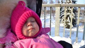 Vauva talvella rattaissa pipo päässä