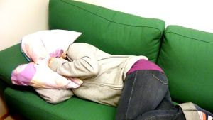Nainen nukkuu sohvalla tyyny puristettuna pään päälle.