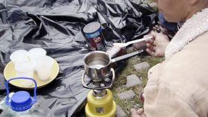 Asunnoton nainen keittää vettä parkkipaikalla.