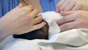 Vanhemmat silittävät vauvaa sairaalan synnytysosastolla.