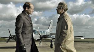 kaksi miestä keskustelee lentokoneen edessä