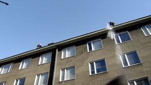 Kaksi miestä tiputtavat lunta pois kerrostalon katolta.