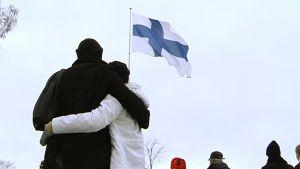 Halaava pariskunta ja muita ihmisiä, taustalla salossa liehuva Suomen lippu.