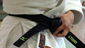 Judoa harrastava sitoo mustaa vyötä kiinni