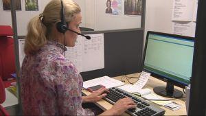 Ensineuvo-puhelinpalvelun työntekijä työpisteellään.