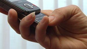 Kännykkä kädessä.