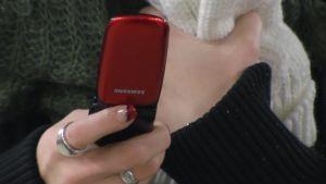 Tyttö näppäilee kännykkää.