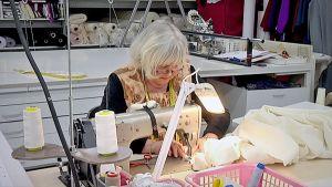 Ateljé Solemniksen työntekijä ompelee koneella vaaleaa kangasta