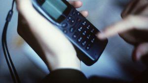 Henkilö näppäilee numeroa kännykkäänsä.