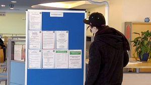 Nuori mies tutkii avointen työpaikkojen ilmoituksia työvoimatoimistossa.