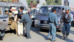 Poliisit tarkastavat autoja ja niiden matkustajia.