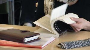 Opiskelija selaa oppikirjaa luokkahuoneessa.