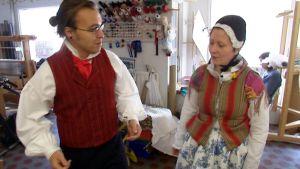 Vasemmalla virolahtelaisen miehen juhlapuku. Oikealla pukuvalmistaja Soja Murron yllä hämäläinen naisten juhlapuku.