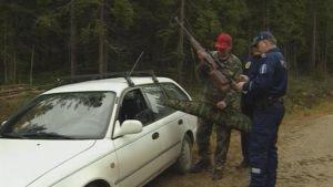 Poliisi tarkastaa metsästäjän aseita.