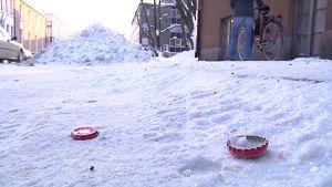 Kuvassa lumisella kadulla kaksi pullonkorkkia ja iso lumikasa, oikealla nainen taluttaa polkupyörää