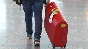 Matkustaja vetää perässään pyörillä kulkevaa matkalaukku lentokentällä.