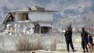 Kaksi tumma-asuista turvamiestä seisoo valvomassa purkutöitä.