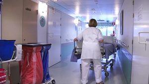 Hoitaja työntää tyhjää sänkyä keskussairaalan käytävällä.