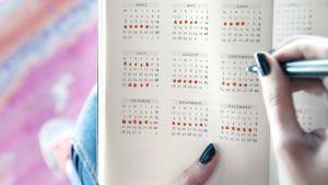 Nainen merkkaa päiviä kalenteriin.