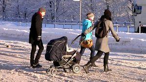 Nainen vetää lastenrattaita suojatiellä. Kaksi muuta jalankulkijaa ylittää myös suojatietä joulukuun aurinkoisena päivänä.