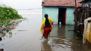 Kalastajanainen kahlaa tulvavedessä Chennaissa.