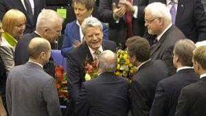 Ihmiset jonottavat onnittelemaan kukkia kädessä pitävää Joachim Gauckia.