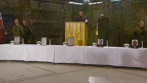 Pappi puhuu. Pöydillä uhrien kuvat.
