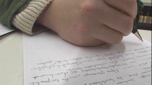 Kuvassa lähikuva kirjoittavasta kädestä ja tekstistä