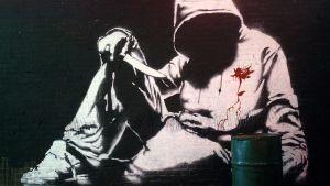 Alikulkutunneliin tehty Banksyn graffitimaalaus, jossa on veitseä pitelevä hupparimies.