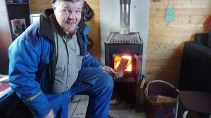 Tuomo Ishoanni lisäämässä puita kamiinaan.