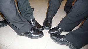Kuvassa miesten jaloissa olevia juhlakenkiä