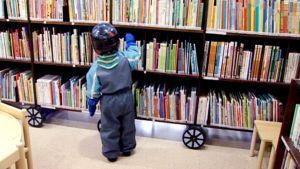 Lapsi katsoo kirjoja kirjaston lastenosastolla.
