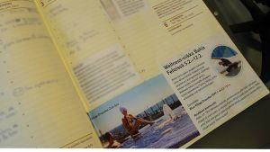 Kuvassa kalenteri, johon on liimattu matkailumainos