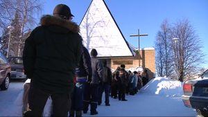 Ihmiset jonottavat ruokajakeluun kirkon edustalla.