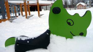Lumeen hautautunut leikkiteline päiväkodin pihalla.