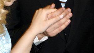 Kuvassa nuoripari käsi kädessä.