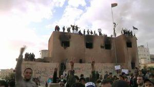 Mielenosoittajia aukiolla ja talon katolla.