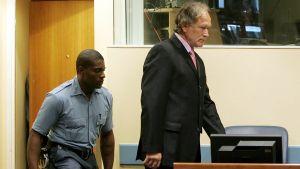 Vartija saattaa miestä oikeudenistuntoon.