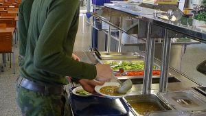 Mies annostelee armeijassa hernekeittoa lautaselleen.