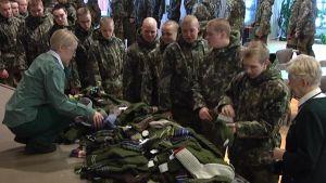 Varusmiehet jonottavat sukkia. Sotilaskotisisaret opastavat.