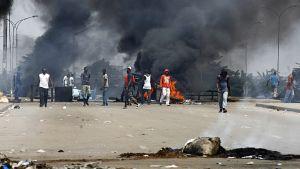 Mielenosoittajat polttavat autonrenkaita Abidjassa Norsunluurannikolla 19.2.2011.
