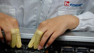 Työntekijä tFoxconnin tehtaan tuotantolinjalla Kiinan Lunghuassa