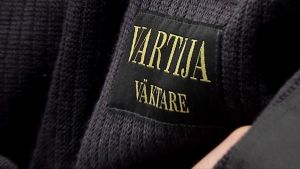 Securitaksen vartijan nimilappu villapaidassa. Vartijan ammattinimike on kirjoiltu myös ruotsiksi, Väktare.