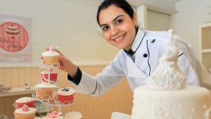 Michelle Kaarakainen kakkuineen yrityksensä tiloissa.