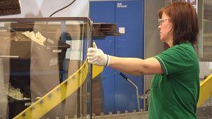 Työntekijä tarkastaa lasia.