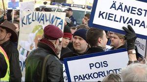 Mielenosoittajia eduskunnan portailla.