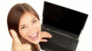 Nainen näyttää peukkua kannettavan tietokoneen ääressä.
