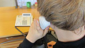 Nuorukainen pitää puhelimen luuria korvallaan.