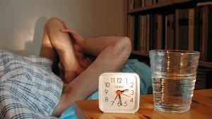 Henkilö sängyssä, edustalla kello.