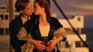 Näyttelijät Leonardo DiCaprio ja Kate Winslet suutelevat Titanicin kannella auringon laskiessa.